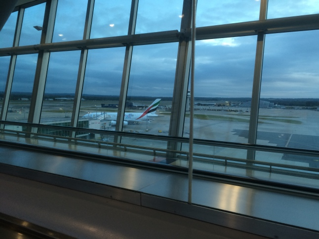 An Emirates Airbus A380, seen through the glass of an airport departure lounge.