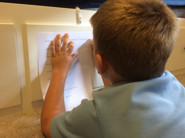 A boy leans against the side of a bed while filling out a questionnaire.